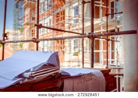 Architectural Drawings Of Residential Edifice Under Construction, Project Plan Placed On Brick Wall