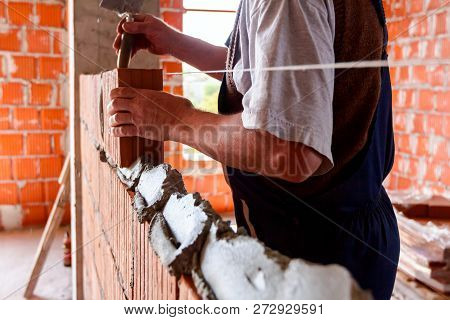 Mason, bricklayer worker is using red blocks to mount a wall next the string line to be straight. poster
