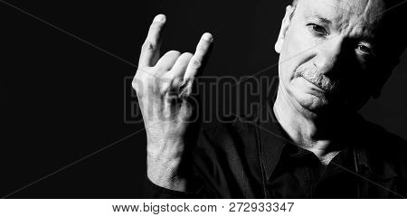 Black And White Portrait Of An Old Man Gesturing On Dark Background With Copy Space. Elderly Old Man
