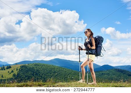 Young Woman Backpacker Hiking Mountain Trail, Walking On Grassy Hill, Wearing Backpack And Sunglasse
