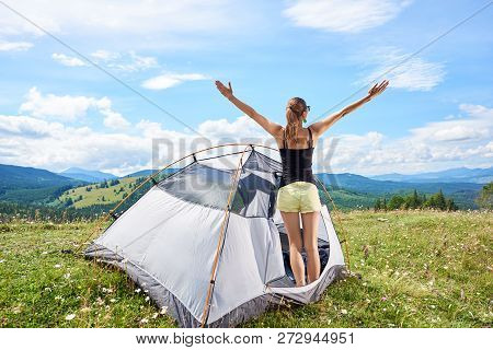 Back View Of Attractive Woman Hiker Hiking Mountain Trail, Standing In Tent, Lifting Hands Up In The