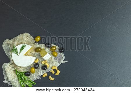 Set Of Cheese Camembert, Black And Green Olives, Quail Eggs, Rosemary, Cashew Nuts, On Black Stone B
