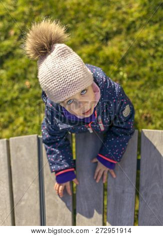 Nice Little Girl With Blue Eyes In A Winter Bunde And Stocking Cap Leaning On A Footbridge Looking U
