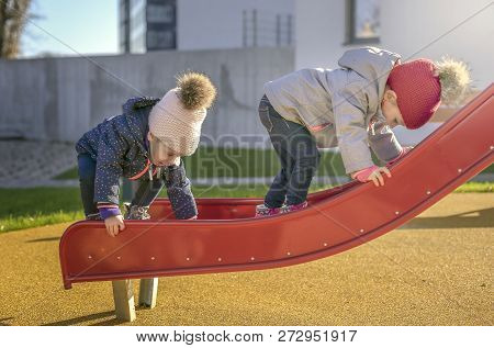 Two Children In Autumn Fall On The Playground For A Slider
