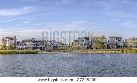 Scenic Landscape With Lakefront Homes Against Sky
