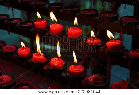 Red Candles With Yellow Flame On Catholic Church Altar. Burning Candle Closeup Photo. In Memoriam Ba