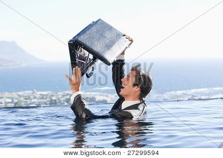 Businessman looking in his briefcase in a swimming pool