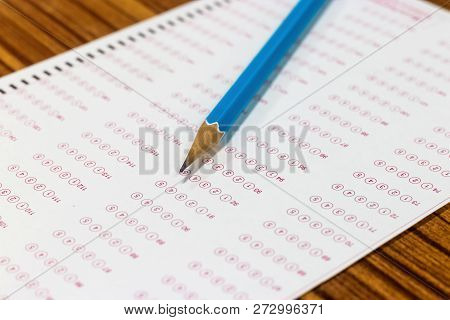 Blue Pencil On Paper Computer Sheet. Standardized Test Form With Answers Bubble. Multiple Choice Ans