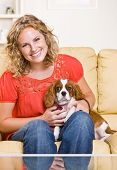Woman sitting on sofa with dog poster