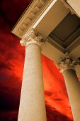 Antique columns on the dramatic red sky background poster