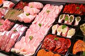 A selection of pork on display in a butchers shop poster