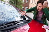 Upset Young Woman Looking At Ticket Fine For Parking Violation On Red Car poster