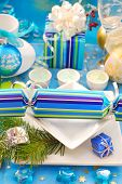 festive table setting with christmas cracker on square shape plates poster