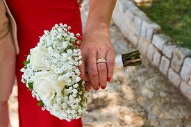 A couple holding a wedding bouquet in front of them, man in white and woman in red dress ring on fin