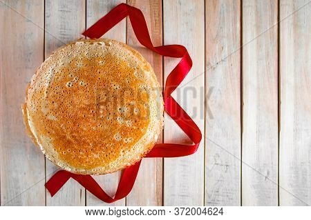 Crepes On A Light Wooden Background And A Red Ribbon. Symbol Of The Sun, Traditional Food For Shrove