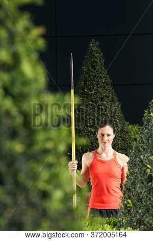 Woman holding javelin standing in landscaped garden portrait