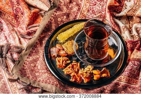 Black Tea In Armudu Glass With Candies With Different Nuts And Crystal Sugar On Metal Tray Over Tabl