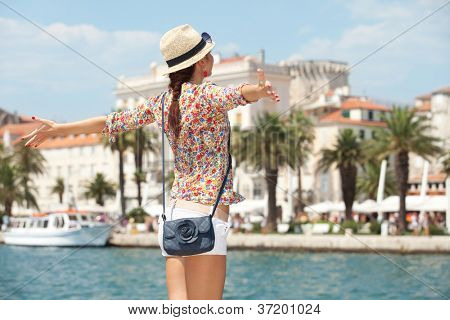 Happy young woman with outstretched hand and see on old town