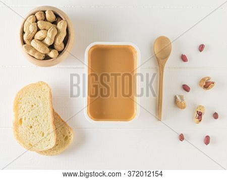 A Spoon, Peanut Seeds And Peanut Paste On A White Table. The View From The Top.
