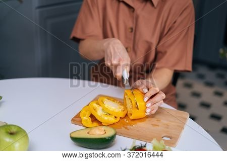 Close-up Of Woman Hands Cutting Fresh Bell Pepper Using Knife On Wooden Cutting Board. Young Woman C