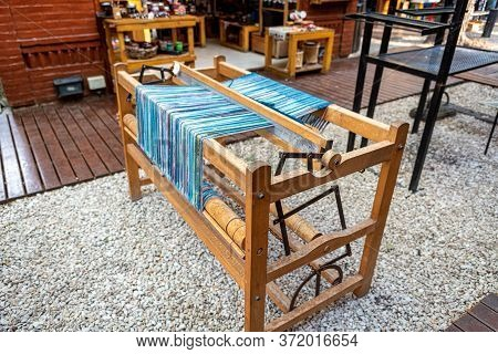 Old Wooden Loom With Light Blue Threads Of Wool
