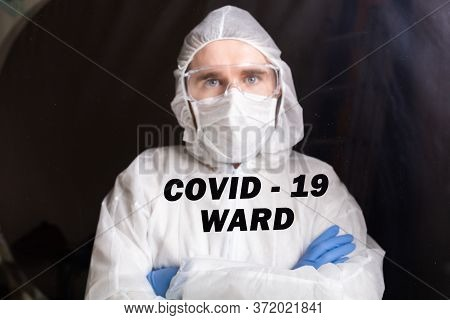 Man In Protective Suit And In Protective Medical Mask Showing Stop Gesture. Epidemiologist Portrait.