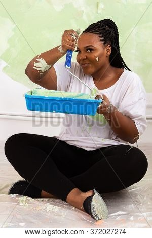 Funny Happy African American Woman Painting Interior Wall With Paint Roller In New House. A Woman Wi