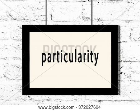 Black Wooden Frame With Inscription Particularity Hanging On White Brick Wall
