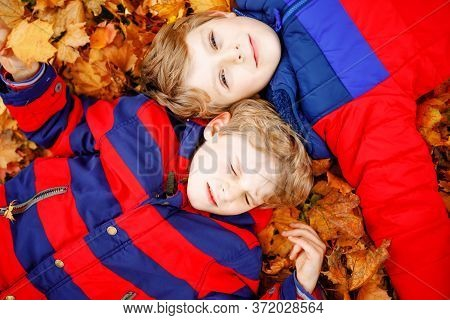 Two Little Kid Boys Lying In Autumn Leaves In Colorful Fashion Fall Clothing. Happy Healthy Siblings