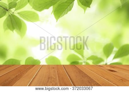 Wood Table Top On Blur Abstract Green Leaf From Garden In The Morning Background.