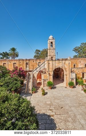 Arched Gate And Wall Of Agia Triad Monastery In Crete In Greece, Rethymno Crete Greece. Green Bushes