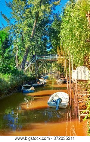 Lush Vegetation, Motor Boats And Old Wooden Pier. Tigra Delta In Argentina, Canals And River System