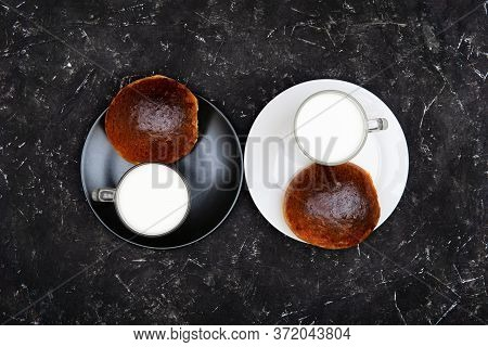 Two Glasses Of Milk And Homemade Sweet Buns On Black And White Plates On A Textured Black Background