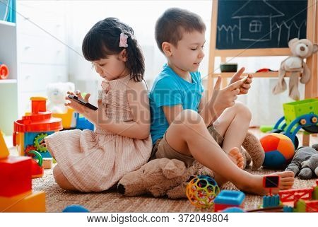 Siblings Children Brother And Sister, Friends Sit On The Floor Of The House In The Childrens Play Ro