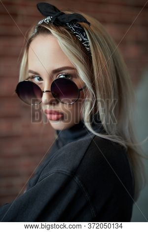 Portrait of a pretty blonde girl in round sunglasses. Beauty, fashion. Modern pin-up style. Optics.