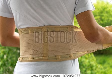 A Teenager Puts On An Orthopedic Corset Or Corset For The Back. Back Pain, Osteochondrosis