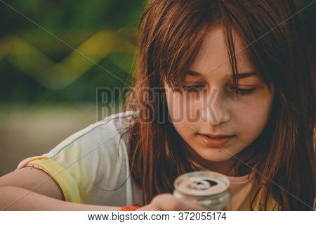 Young Girl Drink Water. Teen Girl Drinks With An Iron Can. A 9-year-old Girl Holds A Drink In Her Ha