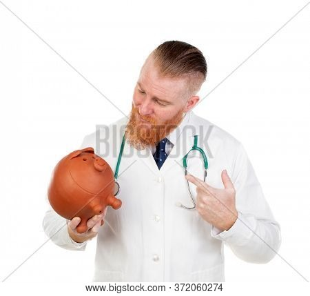 Redhead doctor with a piggybank isolated on a white background
