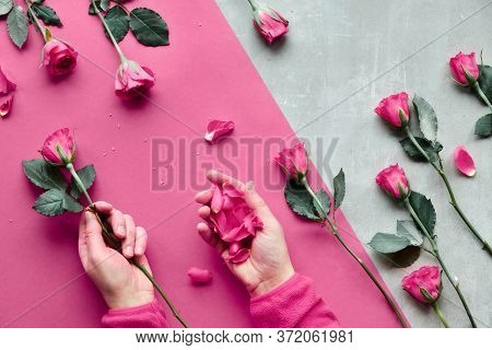 Diagonal Geometric Paper Background On Stone. Flat Lay With Female Hands Holding Pink Rose And Petal