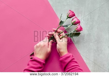 Flat Lay With Two Female Hands Holding Pink Roses On Diagonal Geometric Paper Background On Table. T