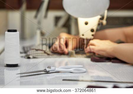 Girl Seamstress Sew On The Sewing Machine. Womens Hands Sewing On The Sewing Machine. Tailoring Proc