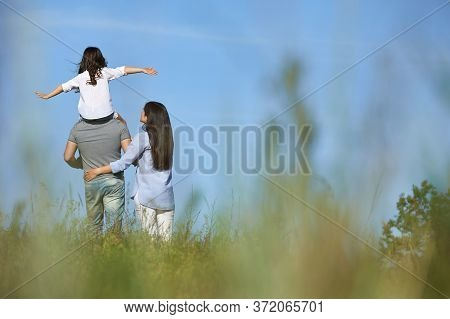 Happy Family Father, Mother And Cute Child Girl Having Fun And Playing In Nature. Daughter Sits On F