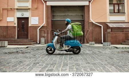Bearded Delivery Man In Helmet With Thermo Bag Or Backpack Riding A Motor Scooter Along The City, De