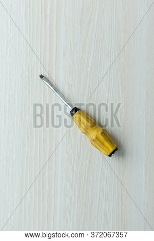 Screwdriver On White Background. Yellow Screwdriver On A Wooden Table.
