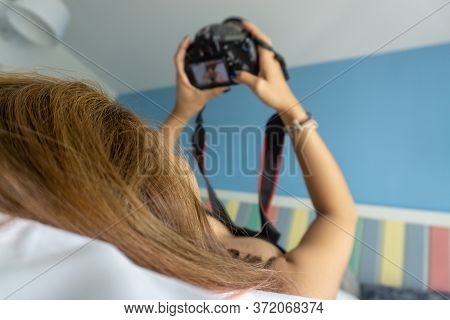 Young Woman Lying On Bed Holding Dslr Camera Looking Photos In Camera In Bedroom. Blured, Soft Focus