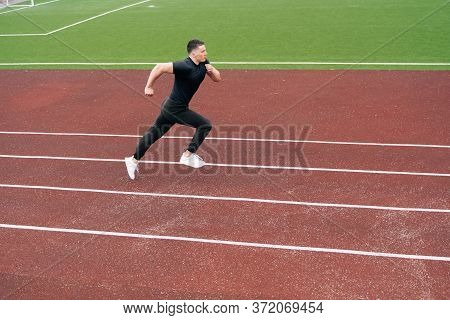 The Sprinter Started Accelerating While Running. A Man Is Engaged In Athletics On A Red Treadmill.