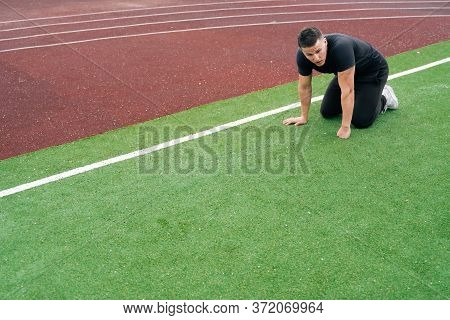 Young Caucasian Male Athlete Is Kneeling In Stadium On Green Grass. The Concept Of Rest Between Appr