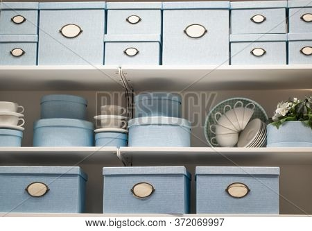 Beautiful Storage Boxes Of Pale Blue Color, On The Shelves With White Porcelain Dishes-plates And Cu