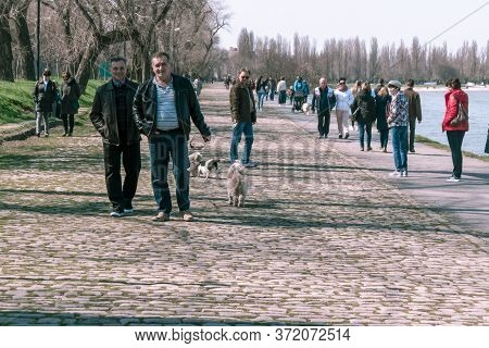 Taganrog, Russia - 07.04.19: Two Men Stroll Along The Embankment On A Holiday. A Lot Of People Walk