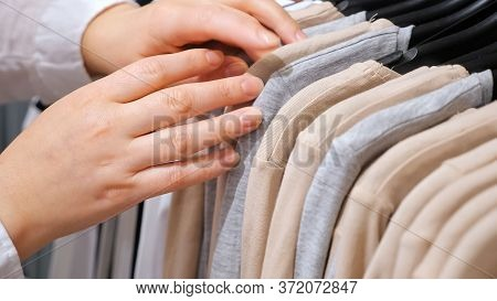 Female Hands Sort Cotton Pullovers On A Hanger In A Clothing Store. Close-up.